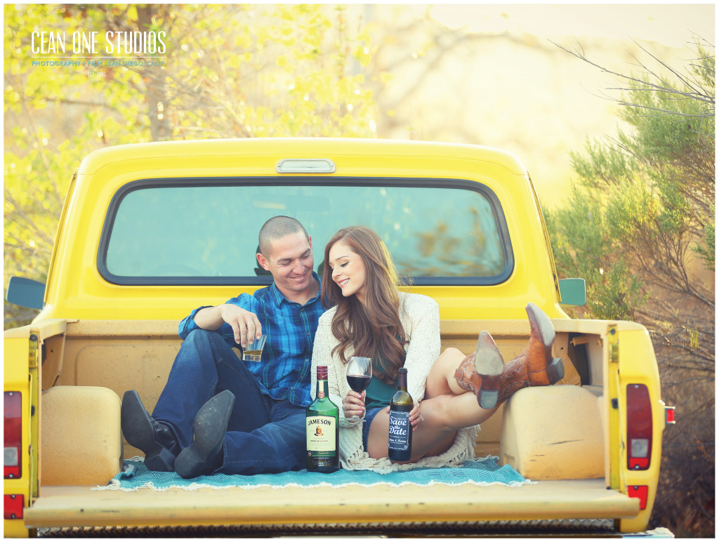 engaged couple smiling on yellow truck