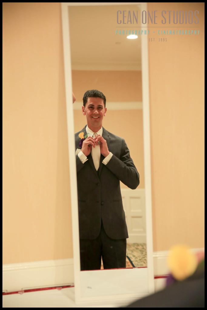 Groom getting dressed in mirror | Hotel del Coronado San Diego Wedding Photographer