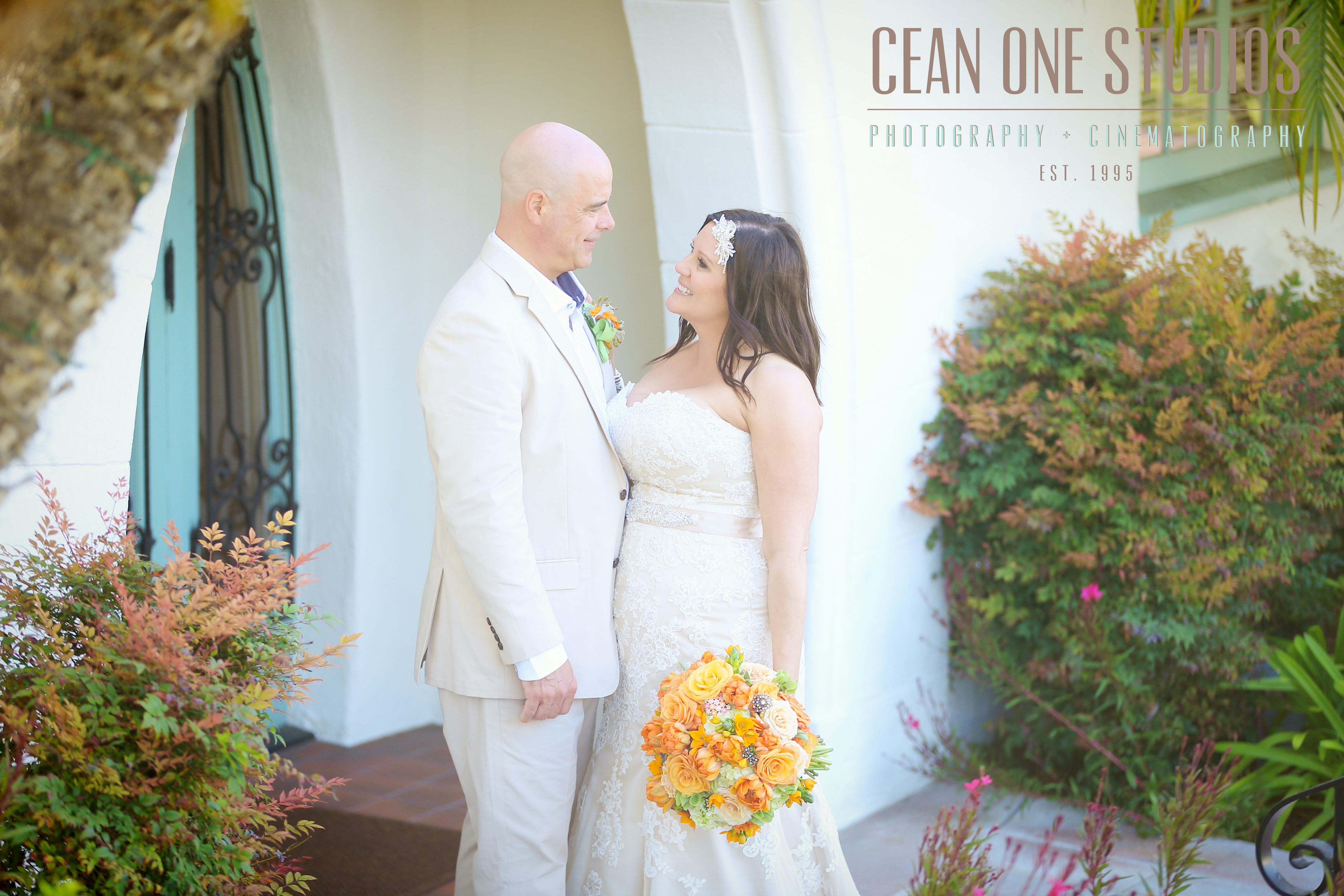 Bride with orange bouquet smiling at groom | Cean One Studios | San Diego Wedding Photographer